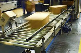 Cardboard packaging boxes travelling down a conveyor belt at a high rate of speed. MIS software for Packaging manages your machines